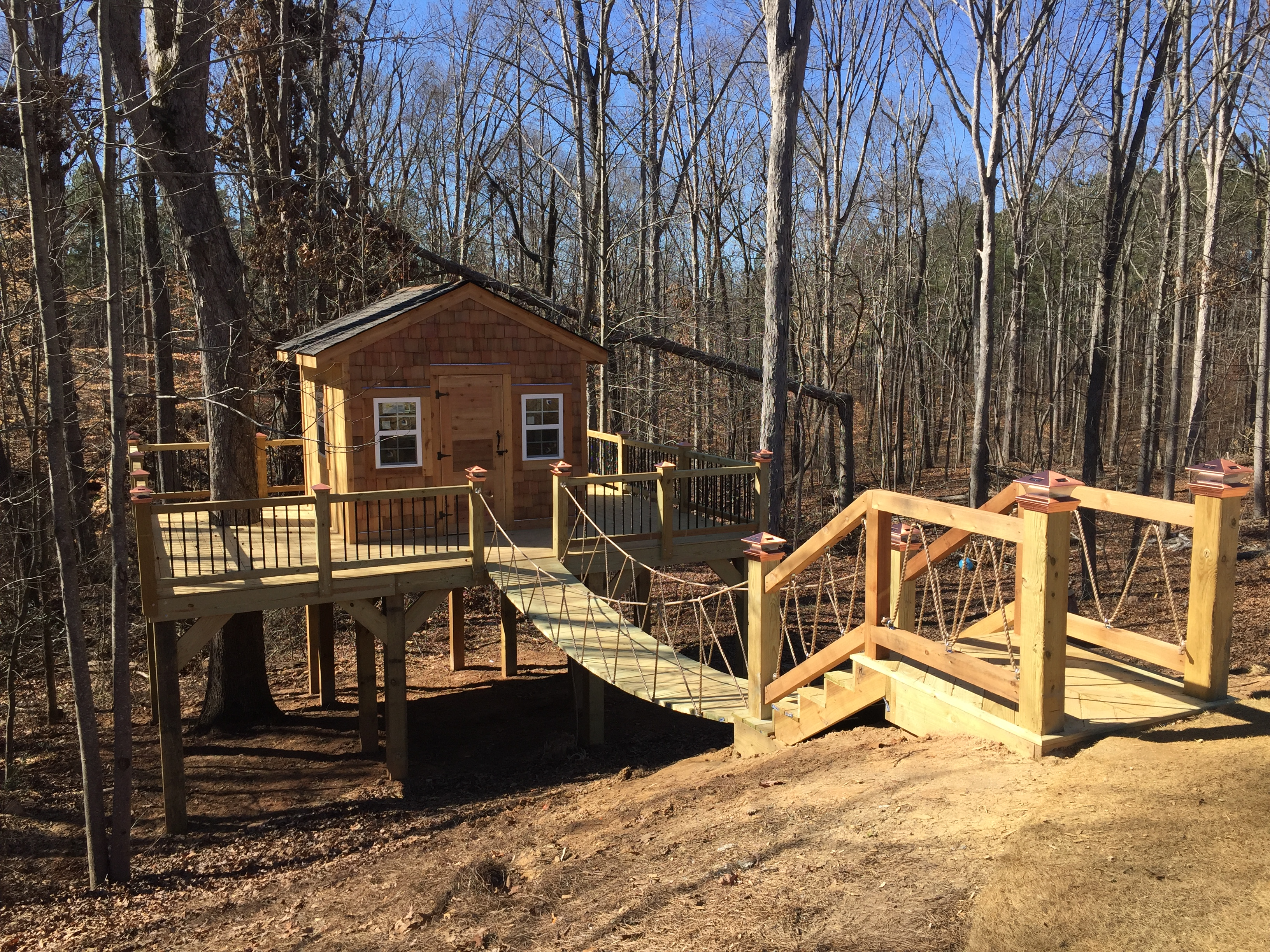 completed treehouse with rope bridge cedar siding Carrollton, GA